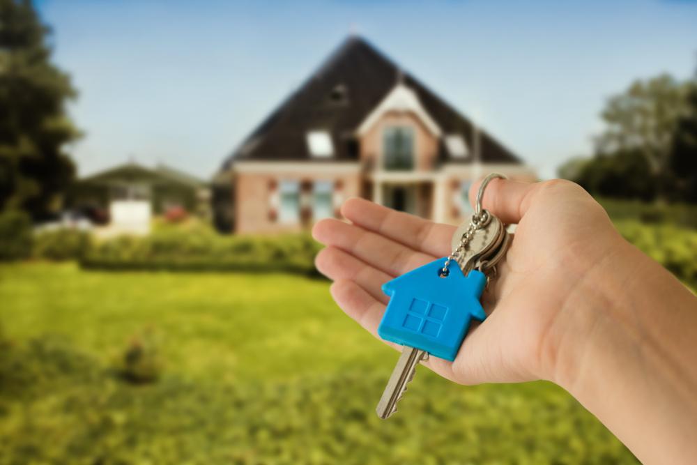klucze z zawieszka domu na tle postawionego domu