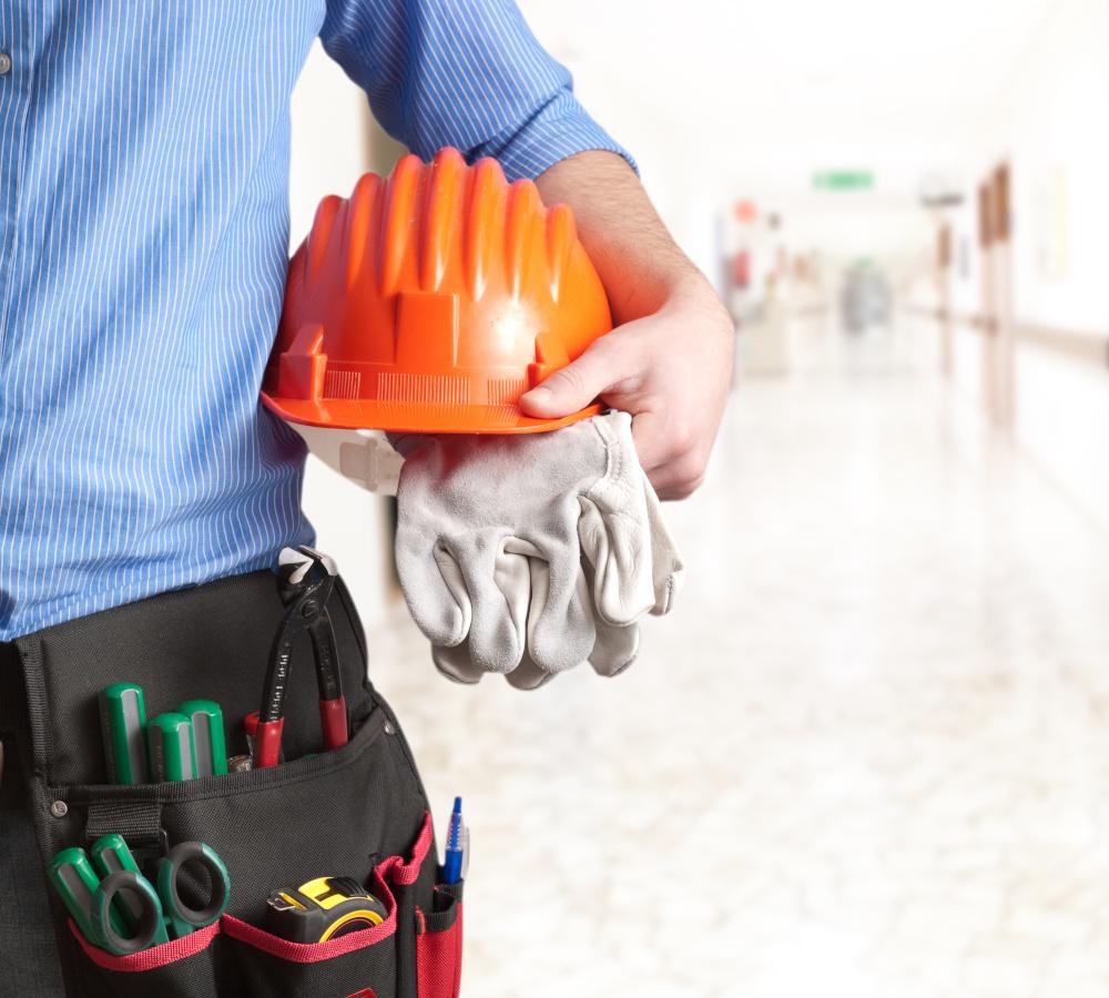 pracownik budowlany ktory w reku trzyma kas i rekawice robocze oraz ma narzedzi w kieszeni