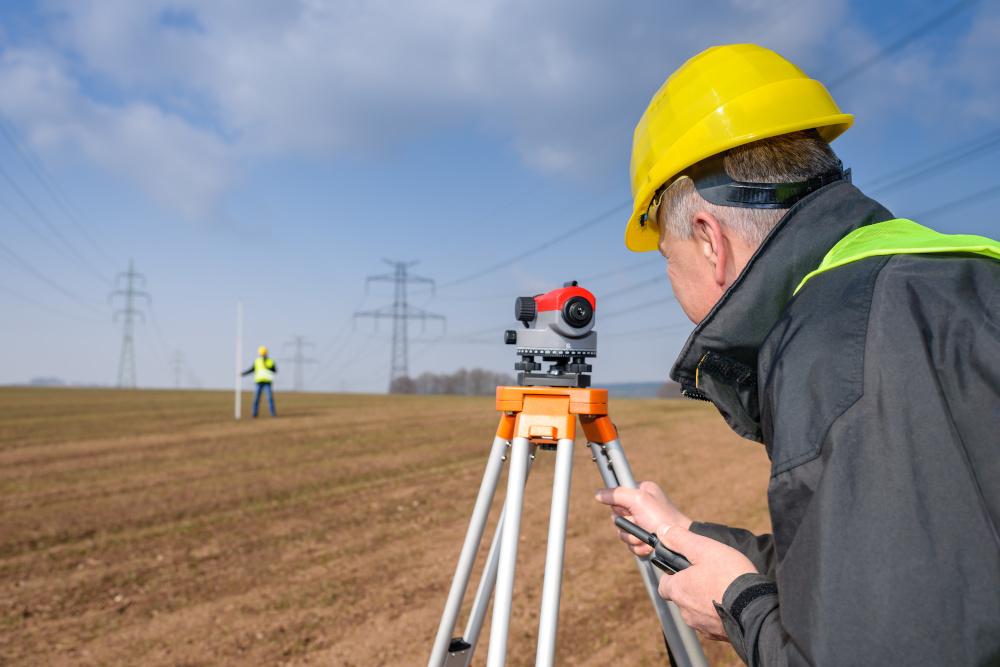 geodeta wykonujacy pomiary na polu