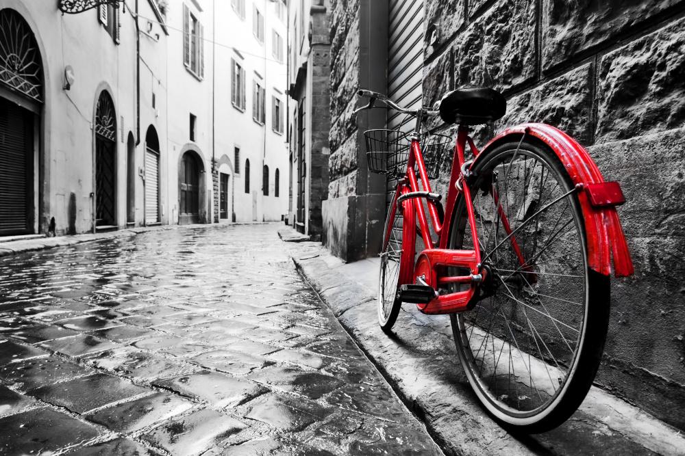 czerwony rower oparty o ścianę budynku