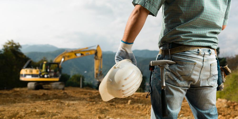robotnik przyglądający się koparce która wykonuje pracę